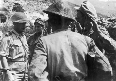 Capt. Weiss (first from left) questions German prisoners of war dragged out of a bunker.