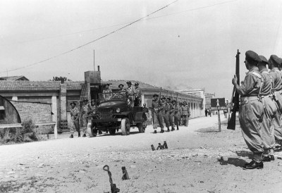 A funeral procession on the way to a cemetery. The casket with Adam Chruściel's body transported by a Studebaker US-6 truck. Soldiers armed with Lee-Enfield guns.